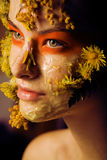 Young woman with yellow floral mask on her face close up, fashion makeup concept Stock Photos