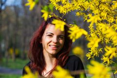 Young woman between yellow flowers Royalty Free Stock Photo