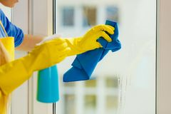 Girl cleaning window at home using detergent rag. Young woman in yellow gloves cleaning window with blue rag and spray detergent. Spring cleanup, housework royalty free stock photos
