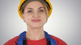 Young woman in yellow hardhat walking on gradient background. stock photo