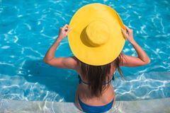 Young woman in yellow hat relaxing at swimming Stock Photo