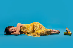Young woman in yellow lying and laughing Stock Photography