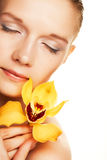 Young woman with yellow orchid Stock Photo