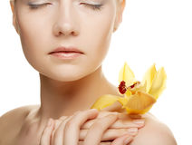Young woman with yellow orchid Royalty Free Stock Photo
