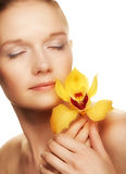 Young woman with yellow orchid Royalty Free Stock Images