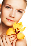 Young woman with yellow orchid Stock Image