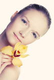 Young woman with yellow orchid Royalty Free Stock Image