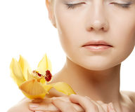 Young woman with yellow orchid Stock Photography