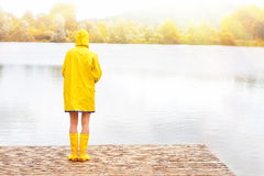 Young woman in yellow raincoat and rubber boots. Standing on lake in autumn stock photos