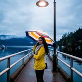 Young woman in a yellow raincoat standing under an umbrella on a rainy day by the ocean. stock photos