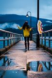 Young woman in a yellow raincoat standing under an umbrella on a rainy day by the ocean. royalty free stock image
