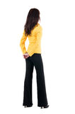 Young woman in yellow suit looking at wall. Royalty Free Stock Photo