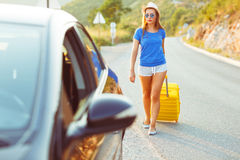 Young woman with a yellow suitcase goes to a car Stock Image