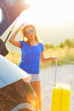 Young woman with a yellow suitcase standing near the trunk of a. A young woman with a yellow suitcase standing near the trunk of a car parked on the roadside Royalty Free Stock Images