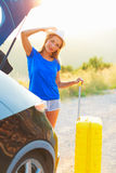 Young woman with a yellow suitcase standing near the trunk of a Stock Image