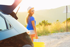 Young woman with a yellow suitcase standing near the trunk of a Royalty Free Stock Photography