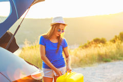 Young woman with a yellow suitcase standing near the trunk of a. A young woman with a yellow suitcase standing near the trunk of a car parked on the roadside Stock Photo