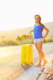 Young woman with a yellow suitcase is traveling on the road hitc Royalty Free Stock Image