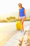 Young woman with a yellow suitcase is traveling on the road hitc Stock Image