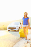 Young woman with a yellow suitcase is traveling on the road hitc Royalty Free Stock Photo