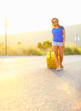 Young woman with a yellow suitcase is traveling on the road hitc Royalty Free Stock Photos