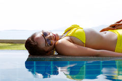 Young woman in yellow swimsuit laying down next to swimming pool Stock Photography