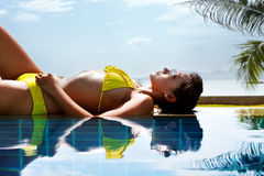 Young woman in yellow swimsuit laying down next to swimming pool Stock Photos