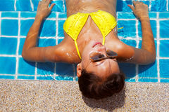 Young woman in a yellow swimsuit laying down in a swimming pool Stock Images