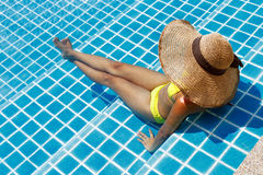 Young woman in a yellow swimsuit seating down in a swimming pool Stock Images