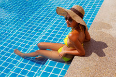 Young woman in a yellow swimsuit seating down in a swimming pool Stock Image