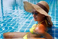 Young woman in a yellow swimsuit seating down in a swimming pool Stock Photos