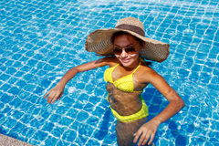 Young woman in a yellow swimsuit standing up in a swimming pool Royalty Free Stock Images
