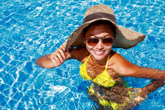 Young woman in a yellow swimsuit standing up in a swimming pool Royalty Free Stock Photography