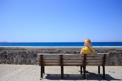 Young woman yellow t-shirt resting on the seafront on a wooden bench stock images