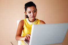 Young woman in a yellow top using a laptop Stock Image