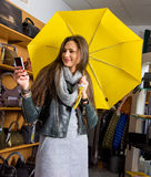 Young woman with yellow umbrella taking selfie Stock Photo