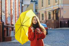 Young woman with a yellow umbrella walking in the street Royalty Free Stock Photos