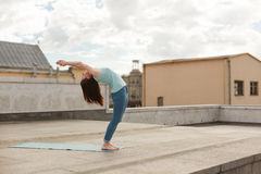 Young woman in a yoga back bend pose Stock Photo