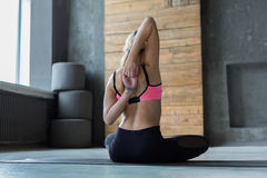 Young woman in yoga class, back stretching Stock Photography