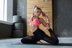Young woman in yoga class, mermaid pose asana Stock Images