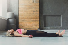 Young woman in yoga class, relax meditation corpse pose. Young slim blond woman in yoga class lay on floor. Girl do meditation corpse pose, savasana for stock image