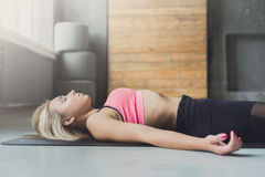 Young woman in yoga class, relax meditation corpse pose Royalty Free Stock Images