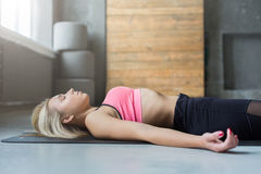 Young woman in yoga class, relax meditation corpse pose Stock Images