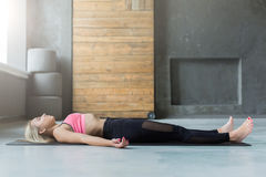 Young woman in yoga class, relax meditation corpse pose Stock Image