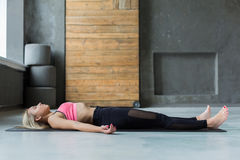 Young woman in yoga class, relax meditation corpse pose Royalty Free Stock Image