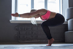 Young woman in yoga class, vinyasa transition to pose. Young slim blond woman in yoga class making asana exercises. Girl do vinyasa transition to pose. Healthy Stock Image