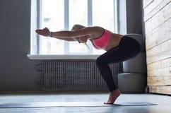 Young woman in yoga class, vinyasa transition to pose. Young slim blond woman in yoga class making asana exercises. Girl do vinyasa transition to pose. Healthy Stock Photos