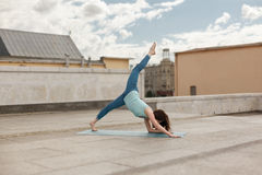 Young woman in a yoga downward-facing dog pose, right leg up Royalty Free Stock Image