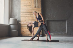 Young woman with yoga instructor in fitness class, triangle pose royalty free stock images