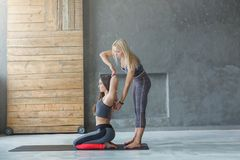 Young woman with yoga instructor in fitness club, gomukhasana stock photos